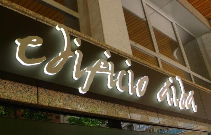 Detalle del rótulo de letras corpóreas de metacrilato y acero instalado en el acceso principal del Edificio Aida en Zaragoza