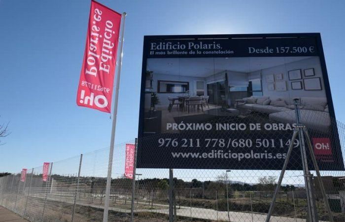 Valla de obra con bandera de obra instalada en solar indicando la próxima construcción de viviendas en Zaragoza