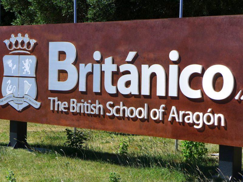 Totem fabricado en Acero Corten con Letras Corpóreas instalado en jardín del acceso principal en el colegio Británico en Zaragoza